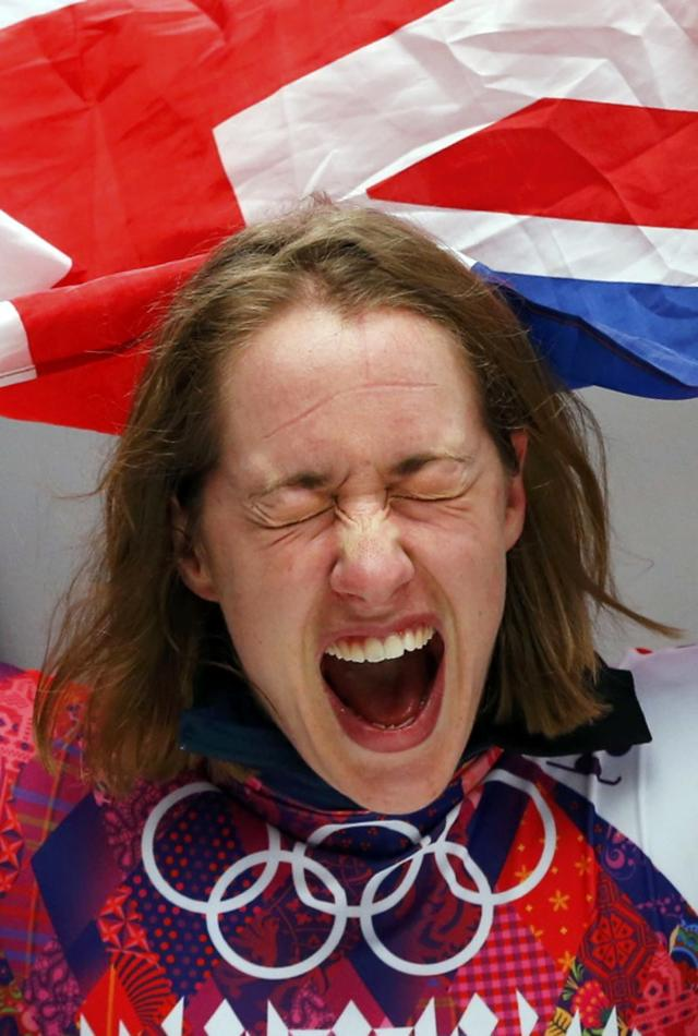 Britain's Elizabeth Yarnold celebrates with the Union flag after winning the women's skeleton event at the 2014 Sochi Winter Olympics February 14, 2014. REUTERS/Arnd Wiegmann (RUSSIA - Tags: SPORT SKELETON OLYMPICS)