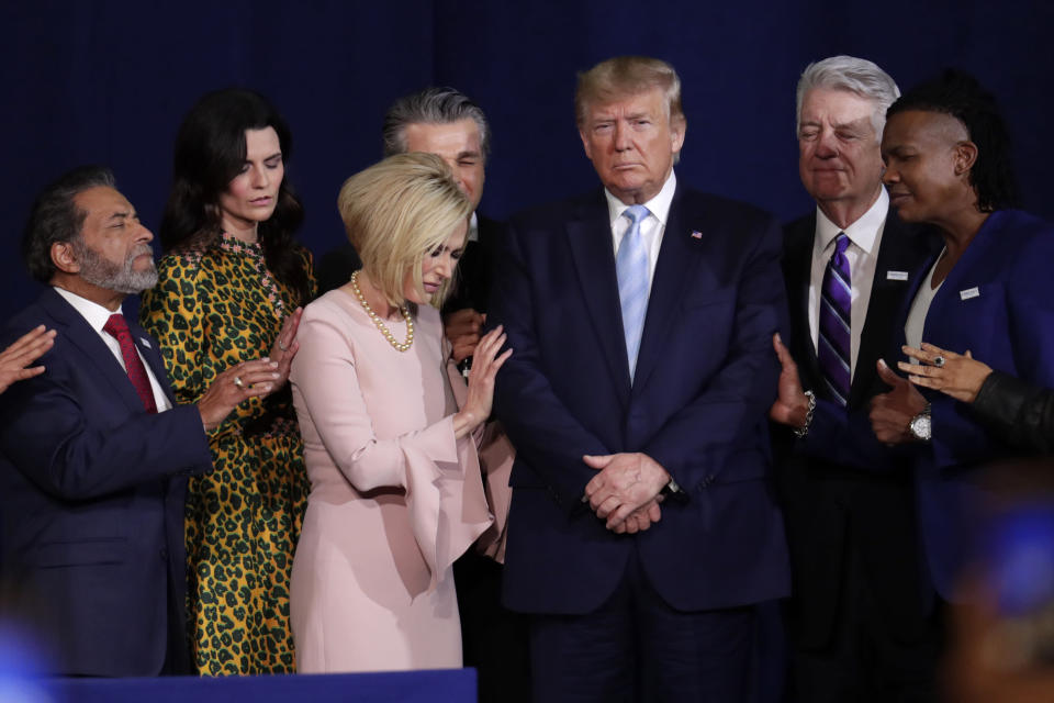 FILE - In this Jan. 3, 2020, file photo, faith leaders pray with President Donald Trump during a rally for evangelical supporters at the King Jesus International Ministry church in Miami. On Friday, March 5, 2021, The Associated Press reported on a manipulated version of this photo circulating online depicting the people praying over a golden idol of former President Donald Trump. While numerous attendees of this year's Conservative Political Action Conference in Orlando, Florida, posed for selfies with a 6-foot-tall golden statue of Trump, the original photo was made over a year earlier. (AP Photo/Lynne Sladky, File)