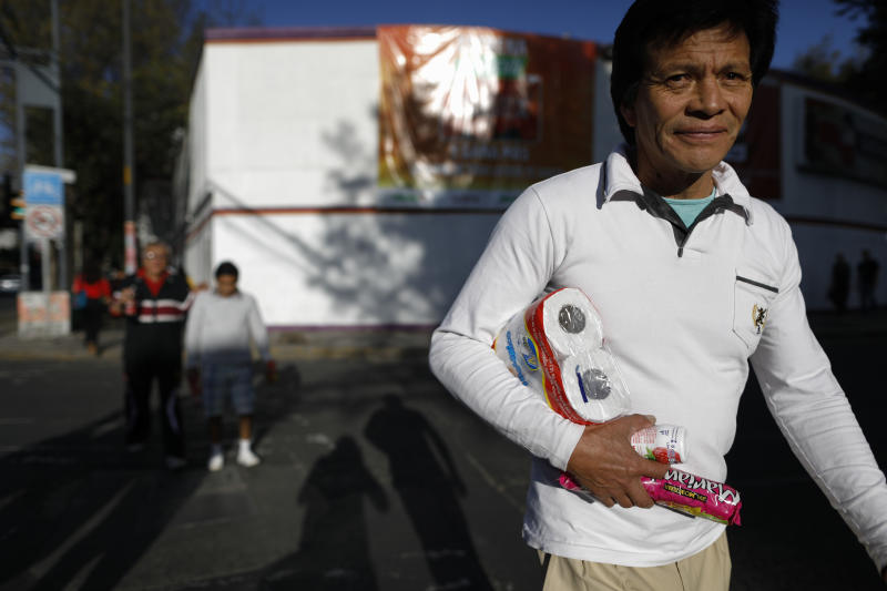A man carries loose items after leaving a grocery store in Mexico City, Wednesday, Jan. 1, 2020. Stores stopped providing disposable plastic bags to their customers in compliance with a city law that took effect with the new year, and shoppers in Mexico's massive capital city could be seen Wednesday carrying handfuls of loose items, as well as purchases packed into reusable shopping bags or used plastic bags brought from home. (AP Photo/Rebecca Blackwell)