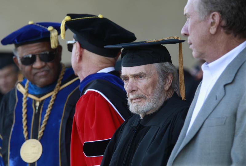 Country music legend Merle Haggard, third from left, waits to be presented with an Honorary Doctorate of Fine Arts from CSUB at the 2013 Arts and Humanities Commencement ceremonies Friday June 14, 2013. At right is Buddy Owens, who accepted the President's Medal on behalf of his father, the late Buck Owens. CSUB President Dr. Horace Mitchell is at left and California State University Trustee Dr. Douglas Faigin, second from left. (AP photo/The Bakersfield Californian, Felix Adamo)