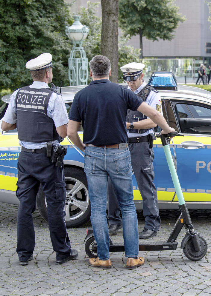 During a police check, an e-scooter driver is warned by the police because he has driven over a pedestrian path in Stuttgart, Germany. | Fabian Sommer—picture-alliance/dpa/AP