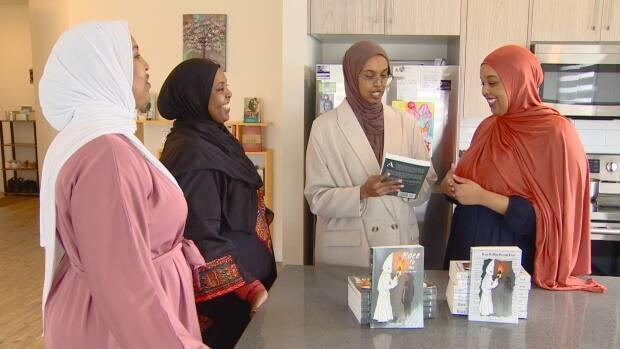 Juweria, Samia, Maymuuna and Aisha Yusuf gather around Aisha's young-adult novel Race to the Finish Line, which is being launched by the Edmonton sisters' new publishing company, Abāyo House, on March 12, 2021.    (Scott Neufeld/CBC - image credit)