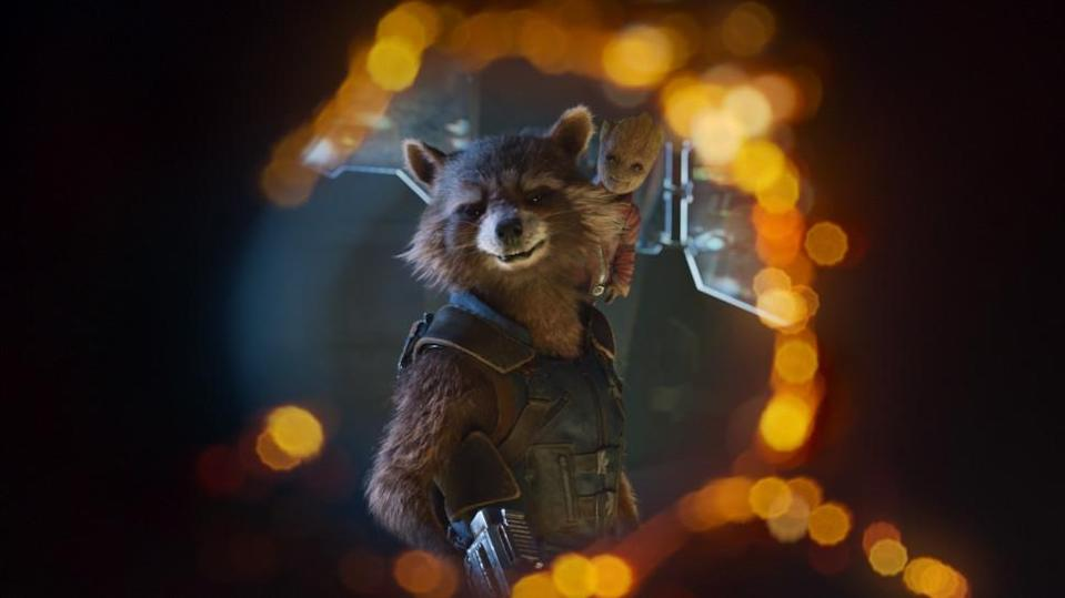 Rocket Raccoon with Baby Groot on his shoulder looks through the hole from a blaster and smiles in Guardians of the Galaxy Vol. 2