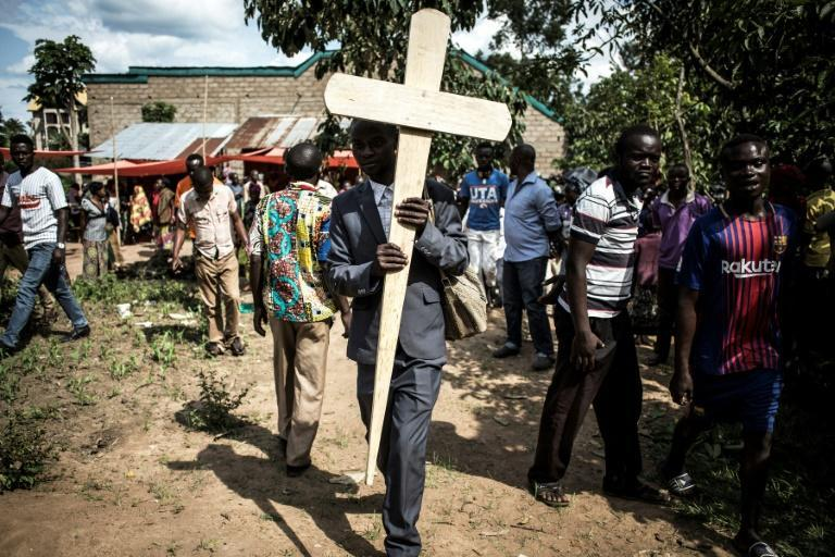 Grief: A relative of a woman killed in a suspected ADF attack in Beni carries a cross to her grave