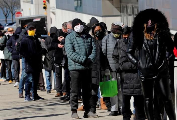 FILE PHOTO: People wait for COVID-19 vaccinations at mass vaccination site in Manhattan in New York