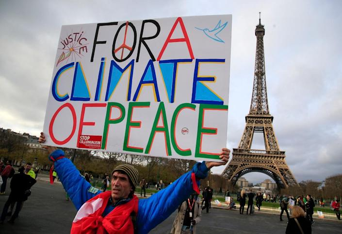 An activist holds a poster during a demonstration near the Eiffel Tower