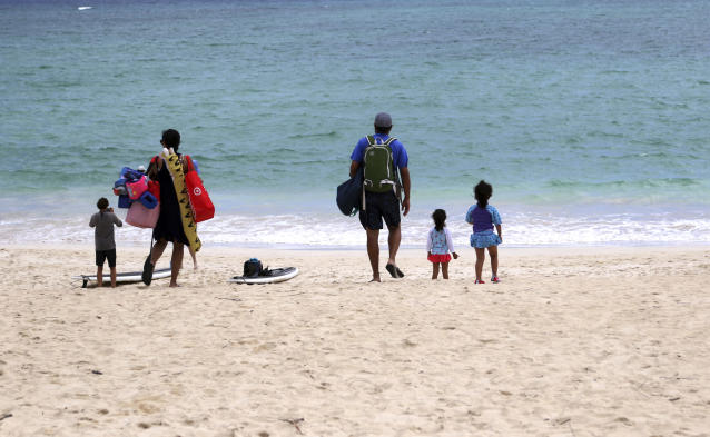 """In this May 15, 2019, photo, people stand near the ocean at Kailua Beach Park in Kailua, Hawaii. In Kailua, the sand is soft and white, the water is clear and calm, and the view is exactly what you might expect from a beach in the Hawaiian Islands. Those are among the reasons the beach has been selected as the best stretch of sand on an annual list of top U.S. beaches. Stephen Leatherman, a coastal scientist and professor at Florida International University, has been drafting the list under the alias """"Dr. Beach"""" since 1991. (AP Photo/Caleb Jones)"""
