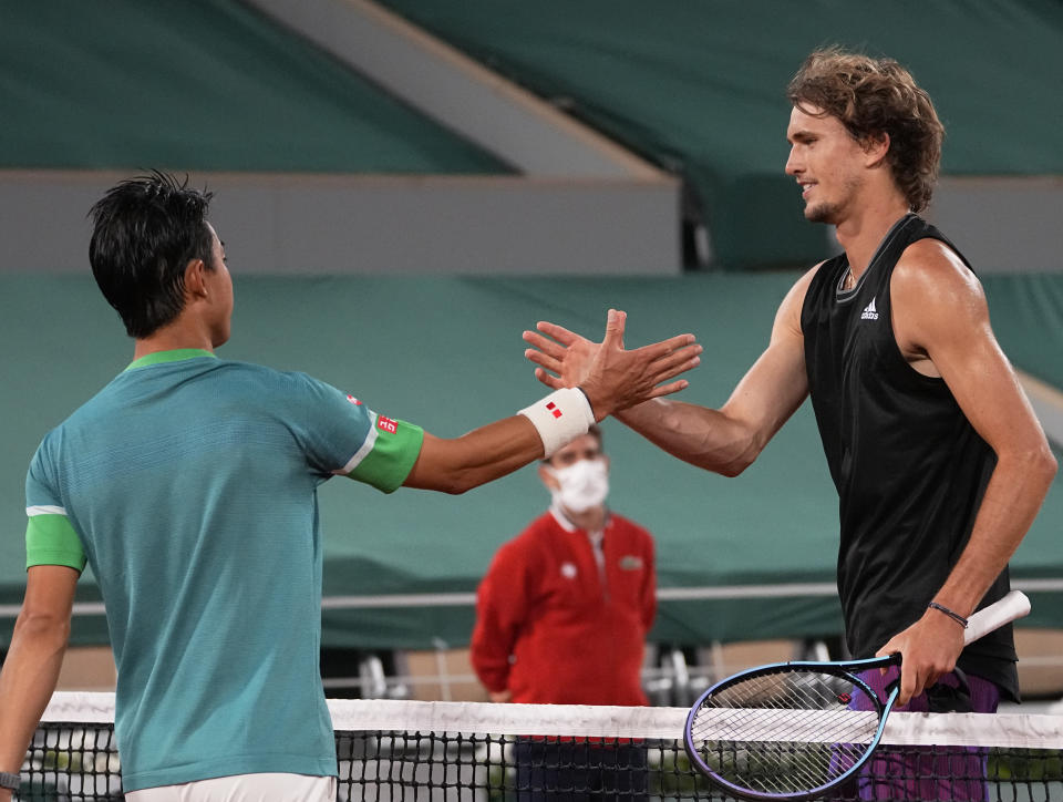 Germany's Alexander Zverev, right, shakes hands with Japan's Kei Nishikori, after he defeated him in their fourth round match on day 8, of the French Open tennis tournament at Roland Garros in Paris, France, Sunday, June 6, 2021. (AP Photo/Michel Euler)