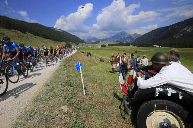 Actors re-enact a scene of WWII as the pack rides during the tenth stage of the Tour de France cycling race over 158.8 kilometers (98.7 miles) with start in Annecy and finish in Le Grand-Bornand, France, Tuesday, July 17, 2018. (AP Photo/Peter Dejong)