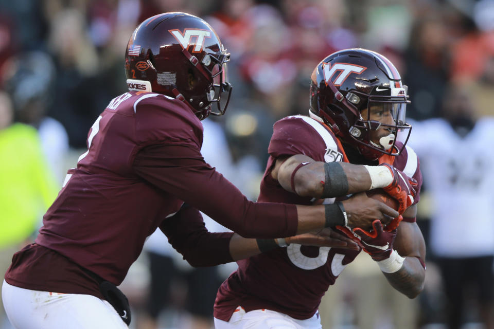 Virginia Tech quarterback Hendon Hooker, left, hands off to Virginia Tech running back Deshawn McClease (33) during the first half of an NCAA college football game against Wake Forest in Blacksburg, Va., Saturday, Nov. 9, 2019. (AP Photo/Steve Helber)