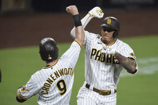San Diego Padres' San Diego Padres Manny Machado is congratulated by Jake Cronenworth (9) after hitting a two-run home run during the fourth inning of a baseball game against the Seattle Mariners, Friday, Sept. 18, 2020, in San Diego. (AP Photo/Denis Poroy)