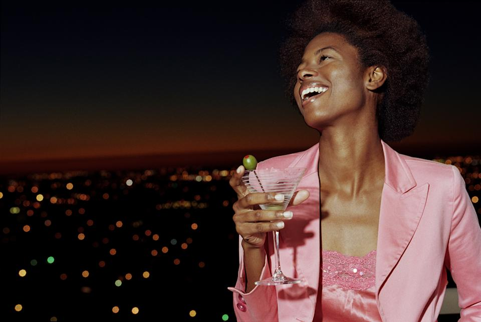 Young woman on balcony holding drink, smiling, night