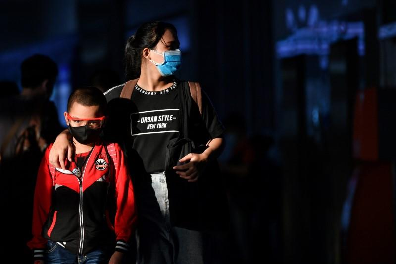 A mother and her son, wearing protective face masks, are seen at a bus station after many workers crowded the terminal station to return to their cities after many activities have been closed due to coronavirus disease (COVID-19) outbreak in Bangkok