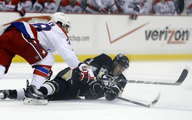 Pittsburgh Penguins' Evgeni Malkin (71), of Russia, is seen through the glass as he tries to control the puck in front of Washington Capitals' Jack Hillen (38) during the second period of an NHL hockey game, Tuesday, March 11, 2014, in Pittsburgh. (AP Photo/Keith Srakocic)
