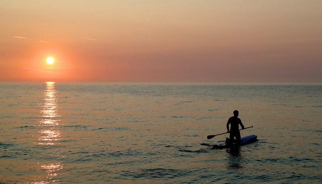 A man sets out into the Channel on a paddleboard as the sun rises in St Margaret's Bay near Dover