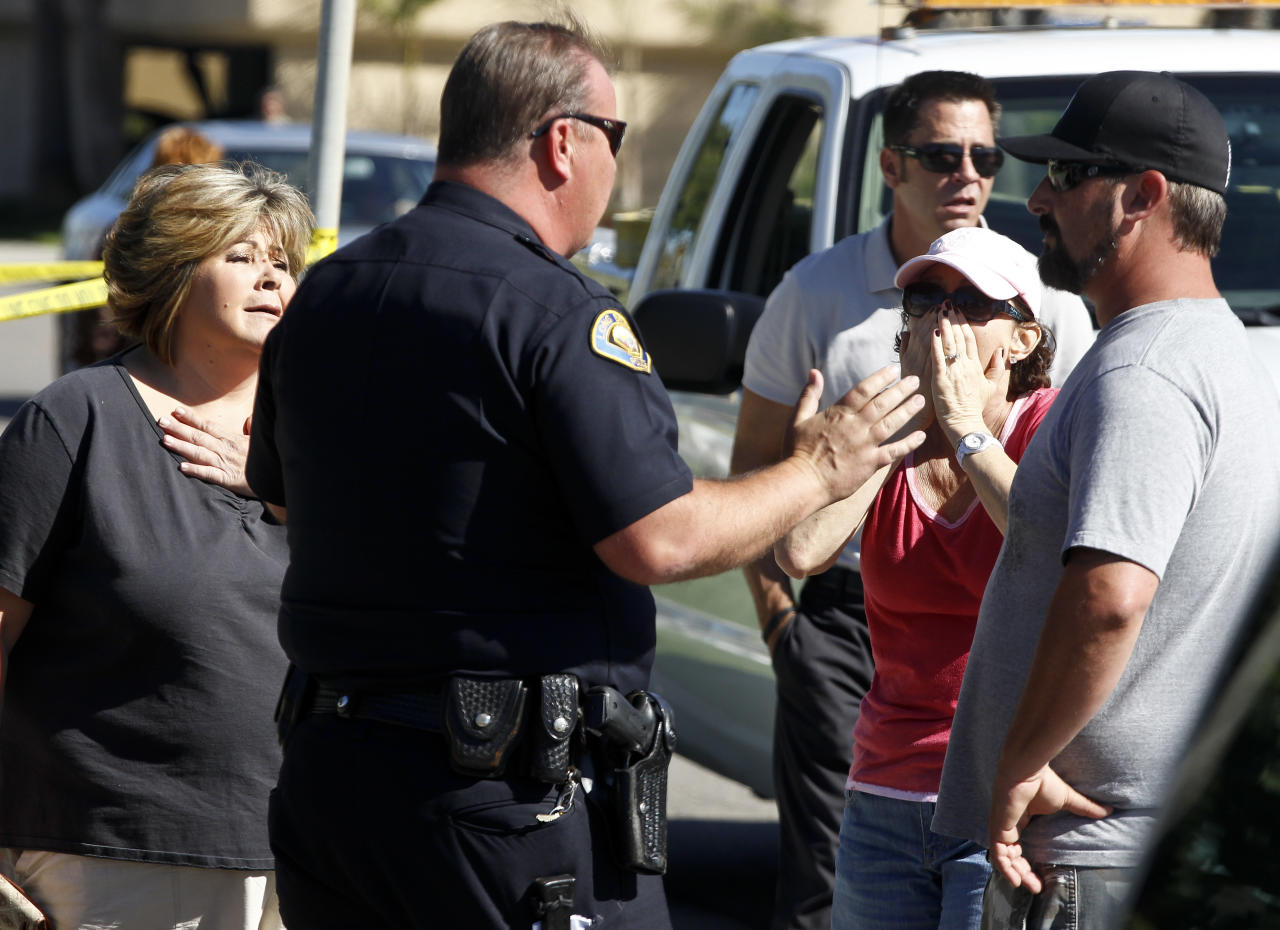 A police officer talks to onlookers near the site where six people were killed and three were wounded in a shooting at a hair salon in Seal Beach, Calif., Wednesday, Oct. 12, 2011. The six deaths were confirmed and the other three victims were taken to a hospital in critical condition, police Sgt. Steve Bowles told The Associated Press. (AP Photo/Chris Carlson)