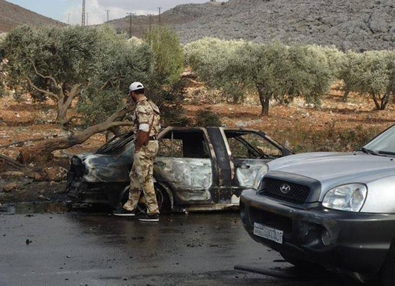 This citizen journalism image provided by Edlib News Network, ENN, which has been authenticated based on its contents and other AP reporting, shows a Syrian rebel with a damaged car at the scene where a car bomb exploded at a crossing point along Syria's volatile border with Turkey, in Bab al-Hawa, Syria, Tuesday, Sept. 17, 2013. (AP Photo/Edlib News Network ENN)