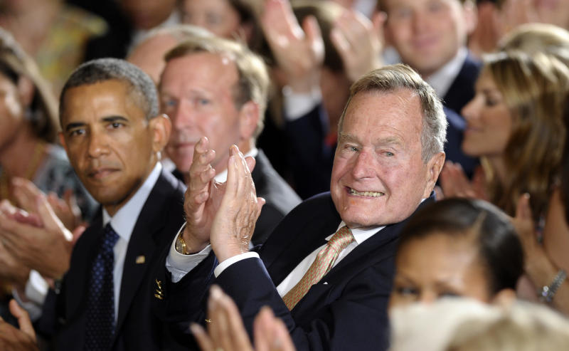 """Former President George H. W. Bush sitting next to President Barack Obama, left, recognizes a member of the audience after presenting the 5,000th Daily Point of Light Award in the East Room of the White House of the White House in Washington, Monday, July 15, 2013. Obama welcomed Bush to the White House in a salute to public service and to the drive for volunteerism that the 41st president inspired with his """"thousand points of light"""" initiative more than two decades ago. (AP Photo/Susan Walsh)"""