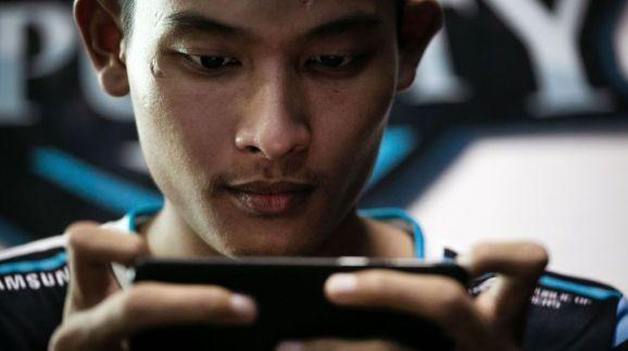 """This photo taken on August 19, 2019 shows eSports professional player Myint Myat Aung, also known as """"Deny"""", playing PlayerUnknown's Battleground (PUBG) on his mobile phone in Yangon. - Myanmar's gaming scene is mushrooming, but frequent power cuts are holding players back in the emerging democracy. (Photo by Sai Aung MAIN / AFP) / TO GO WITH Myanmar-eSports-youth, FEATURE by Lapyae KO and Dene-Hern CHEN (Photo credit should read SAI AUNG MAIN/AFP via Getty Images)"""