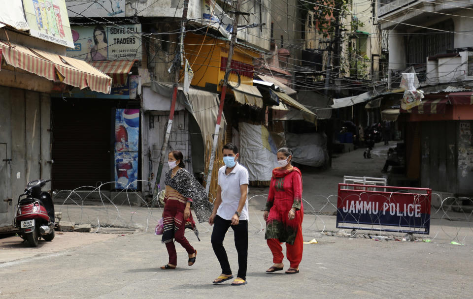Indians wearing face masks as a precaution against the coronavirus walk past closed market during reimposed weekends lockdown to prevent the spread of new coronavirus in Jammu, India, Saturday, July 25, 2020. India is the third hardest-hit country by the pandemic in the world after the United States and Brazil. (AP Photo/Channi Anand)