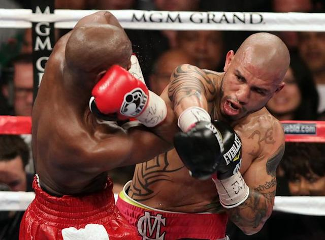 Miguel Cotto (R) grazes Floyd Mayweather Jr. during their WBA super welterweight title fight at the MGM Grand in Las Vegas Saturday, May 5, 2012. Mayweather won the WBA super welterweight title in a 12 round unanimous decision. AFP PHOTO / John GurzinskiJOHN GURZINSKI/AFP/GettyImages