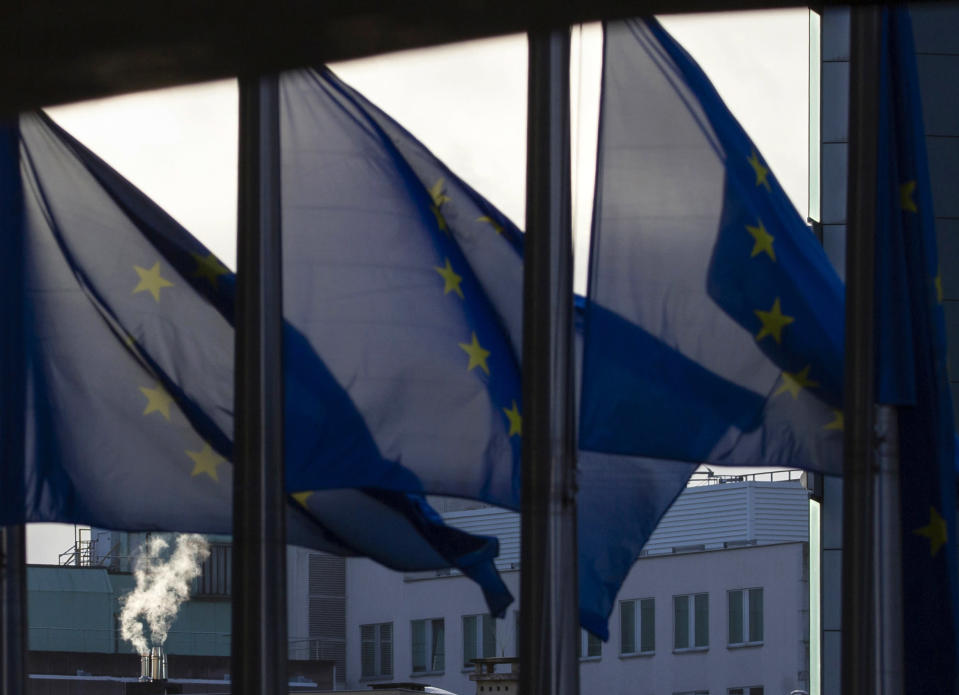 Smoke rises from a chimney behind EU flags fluttering in the wind outside EU headquarters in Brussels, Thursday, Dec. 24, 2020. European Union and British negotiators worked through the night and into Christmas Eve in the hopes of putting the finishing touches on a trade deal that should avert a chaotic economic break between the two sides on New Year's Day. (AP Photo/Virginia Mayo)