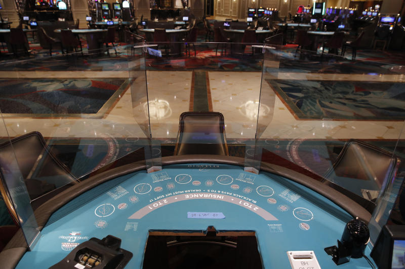 Acrylic barriers separate player's seats as a coronavirus safety precaution at a blackjack table in the closed Bellagio hotel and casino, Wednesday, May 20, 2020, in Las Vegas. Casino operators in Las Vegas are awaiting word when they will be able to reopen after a shutdown during the coronavirus outbreak. (AP Photo/John Locher)