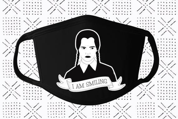 """<br><br><strong>JeepsySouls</strong> Wednesday Addams I Am Smiling Face Mask, $, available at <a href=""""https://go.skimresources.com/?id=30283X879131&url=https%3A%2F%2Fwww.etsy.com%2Flisting%2F846323418%2Fwednesday-addams-i-am-smiling-face-mask"""" rel=""""nofollow noopener"""" target=""""_blank"""" data-ylk=""""slk:Etsy"""" class=""""link rapid-noclick-resp"""">Etsy</a>"""
