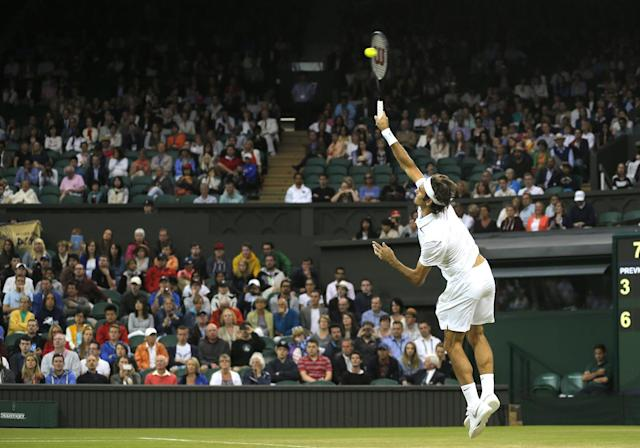 Roger Federer of Switzerland serves to Gilles Muller of Luxembourg during their men's singles match at the All England Lawn Tennis Championships in Wimbledon, London, Thursday, June 26, 2014. (AP Photo/Sang Tan)