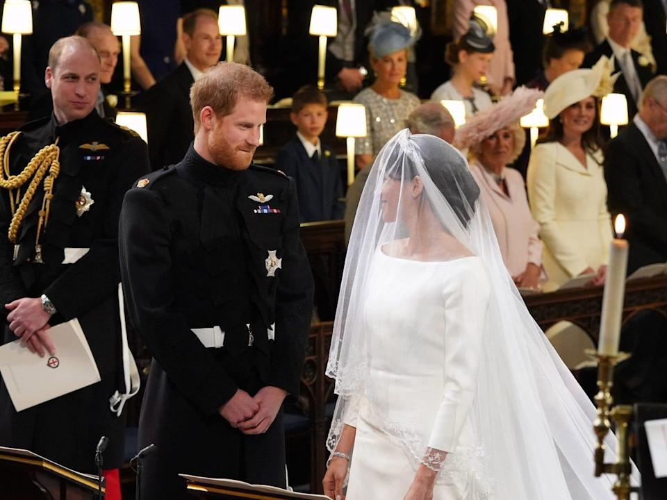 Prince Harry and Meghan Markle at their wedding. Harry bites his lip as he looks at Markle.