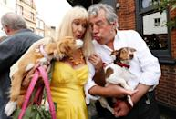 FILE PHOTO: Python actor Terry Jones carries his dog Nancy and blows a raspberry at Talula, the dog of Python actor Carol Cleveland outside the Angel pub in Highgate, north London