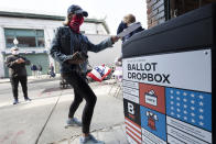 A woman places her ballot in a dropbox after voting at Fenway Park, Saturday, Oct. 17, 2020, in Boston. (AP Photo/Michael Dwyer)