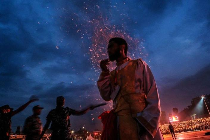 An Orthodox devotee stands in front of a bonfire as policemen stand in the back during the celebrations of the eve of the Ethiopian Orthodox holiday of Meskel, that commemorates the discovery in the fourth century of the True Cross by the Roman Empress Helena, in the city of Addis Ababa, Ethiopia, on September 26, 2021.