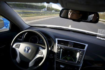 Li Zengwen, a development engineer at Changan Automobile, is reflected in a mirror as a self-driving car from the company is on self-driving mode during a test drive on a highway in Beijing, China, April 16, 2016. REUTERS/Kim Kyung-Hoon