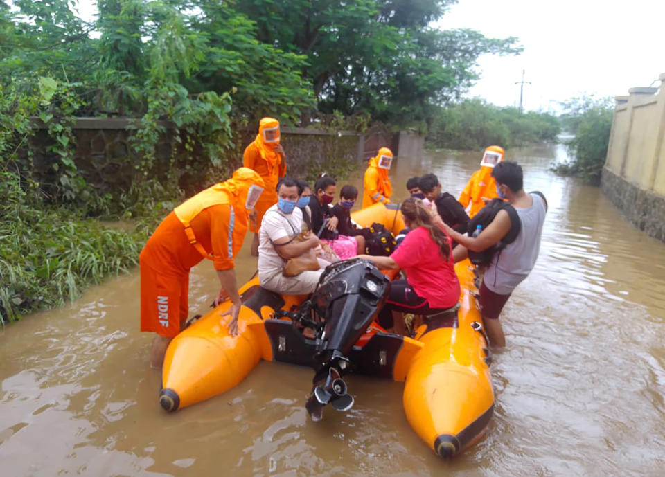 This photograph provided by India's National Disaster Response Force (NDRF) shows NDRF personnel rescuing people stranded in floodwaters in Bhiwandi, in the western Indian state of Maharashtra, Thursday, July 22, 2021. Landslides triggered by heavy monsoon rains hit parts of western India, killing at least five people and leading to the overnight rescue of more than 1,000 other people trapped by floodwaters, an official said Friday. (National Disaster Response Force via AP)