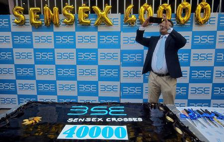 A man uses his mobile phone to take pictures next to a cake to celebrate the Sensex index rising to over 40,000, in Mumbai, India, May 23, 2019. REUTERS/ Francis Mascarenhas