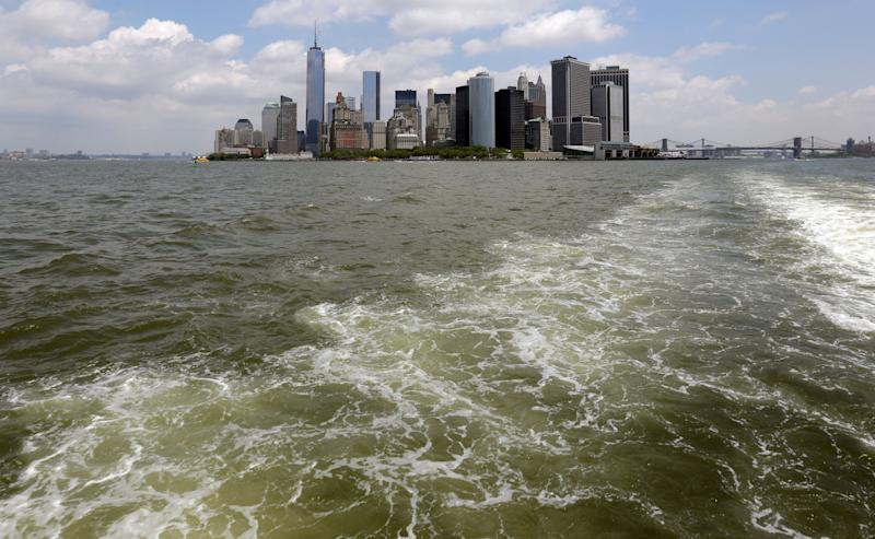 Lower Manhattan is visible from the Staten Island Ferry, in New York's Upper Bay, Tuesday, June 11, 2013. Giant removable floodwalls would be erected around lower Manhattan, and levees, gates and other defenses would be built elsewhere around the city under a nearly $20 billion plan proposed Tuesday by Mayor Michael Bloomberg to protect New York from storms and the effects of global warming. (AP Photo/Richard Drew)