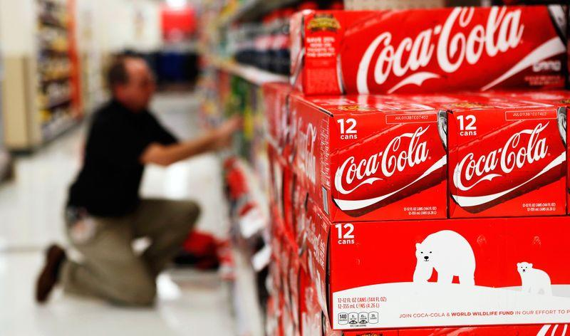 An employee arranges bottles of Coca-Cola at a store in Alexandria in this file photo