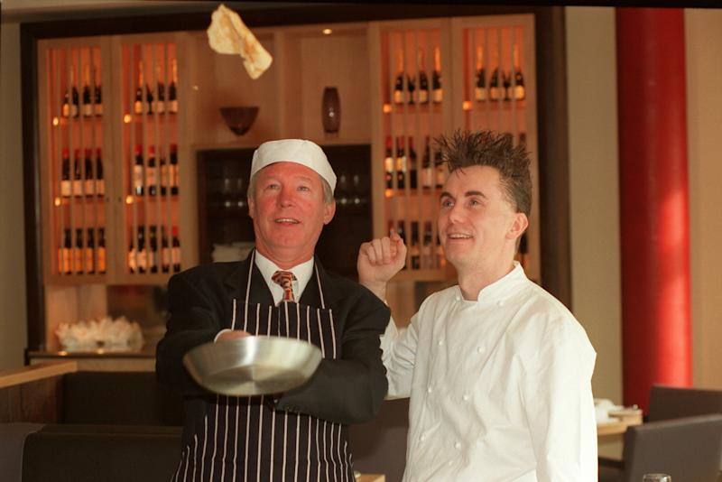 Manchester United manager Alex Ferguson (left) tosses a pancake at the opening of the Manchester United restaurant, cheered on by chef Gary Rhodes (right) (Photo by Peter Wilcock/EMPICS via Getty Images)