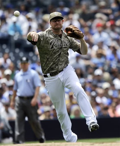 San Diego Padres third baseman Chase Headley makes the running throw after fielding a slow roller hit by Los Angeles Dodgers' Yasiel Puig in the fourth inning of a baseball game in San Diego, Sunday, June 23, 2013. The throw was wide but Puig was given a hit on the play. (AP Photo/Lenny Ignelzi)