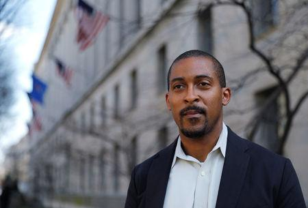 Johnathan Smith, formerly a staff attorney in the Civil Rights Division of the Obama Administration Justice Department, who is now the legal director of Muslim Advocates, stands in front of the U.S. Justice Department headquarters building where he used to work in Washington.  REUTERS/Jim Bourg