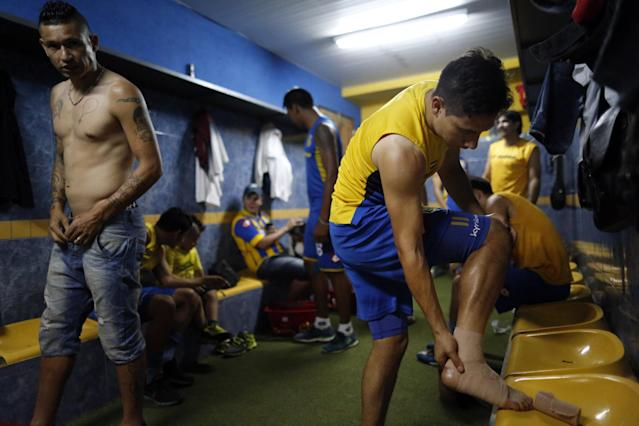 In this Oct. 18, 2014 photo, soccer players Fabio Escobar, left, and Oscar Ruiz from the Deportivo Capiata team prepare for practice in Capiata, Paraguay. The young soccer club formed six years ago beat Boca 1-0 at its famed La Bombonera stadium in Buenos Aires on Oct. 15, and will face them in a second leg match on Thursday, Oct. 23. (AP Photo/Jorge Saenz)