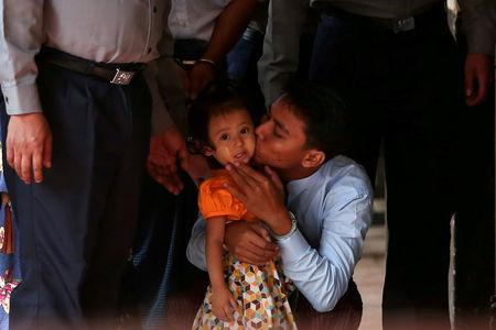Detained Reuters journalist Kyaw Soe Oo kisses his daughter as he is escorted by police for a court hearing in Yangon, Myanmar, February 21, 2018. REUTERS/Stringer
