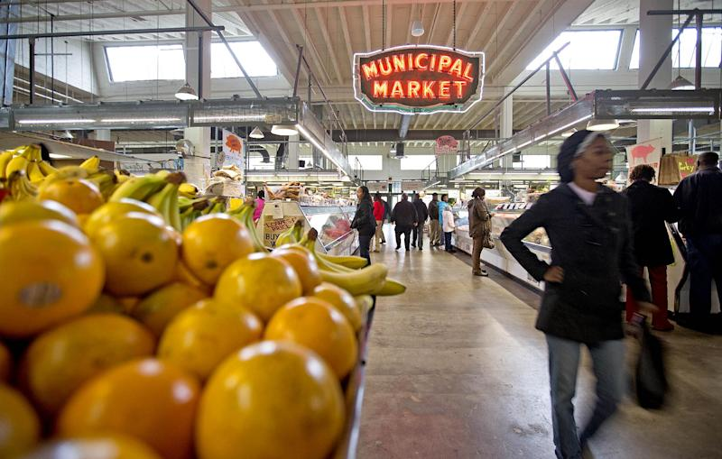 FILE - This Dec. 20, 2013 file photo shows shoppers passing through the Sweet Auburn Curb Market in Atlanta. Look no further than your dinner plate to understand how the sweeping farm bill affects you. About 15 percent of the money in the new law, signed by President Obama Friday, will go to farmers to help them grow the food you eat. Most of the rest of the money in the almost $100 billion-a-year law will go to food stamps that help people buy groceries. (AP Photo/David Goldman, File)