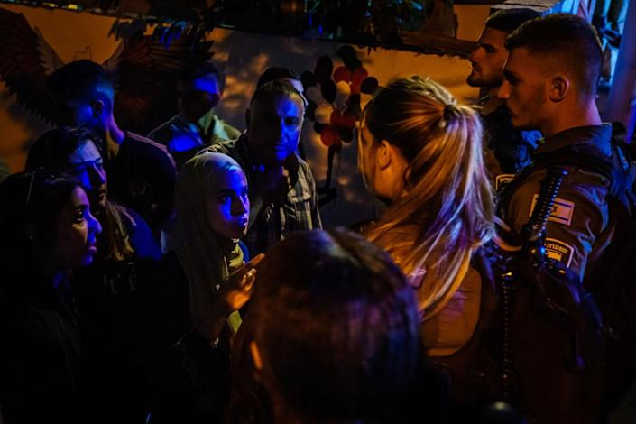 Muna Kurd, center left, and other Palestinians speak to Israeli security officers.