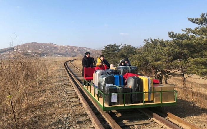 Russian diplomats and family members leave North Korea to Russia using a hand-pushed rail trolley due to Pyongyang's coronavirus restrictions - AFP