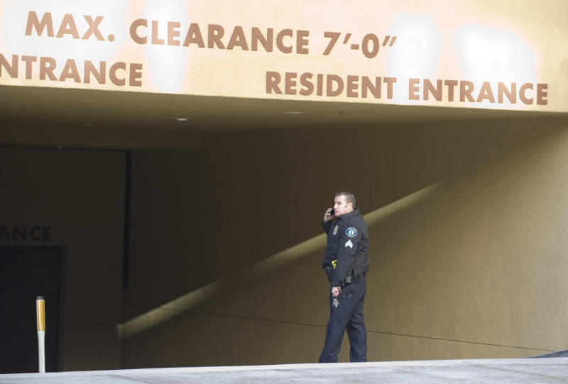 An Irvine police officer talks on the phone Monday, Feb. 4, 2013 at the entrance to the parking garage where two people were found shot to death in their car in Irvine, Calif., Sunday night, Feb. 3. Police in Orange County say they have no motive for a shooting that killed California State University, Fullerton assistant college basketball coach Monica Quan and her fiance, Keith Lawrence, whose bodies were found in a parked car. (AP Photo/The Orange County Register, Sam Gangwer) MAGS OUT; LOS ANGELES TIMES OUT