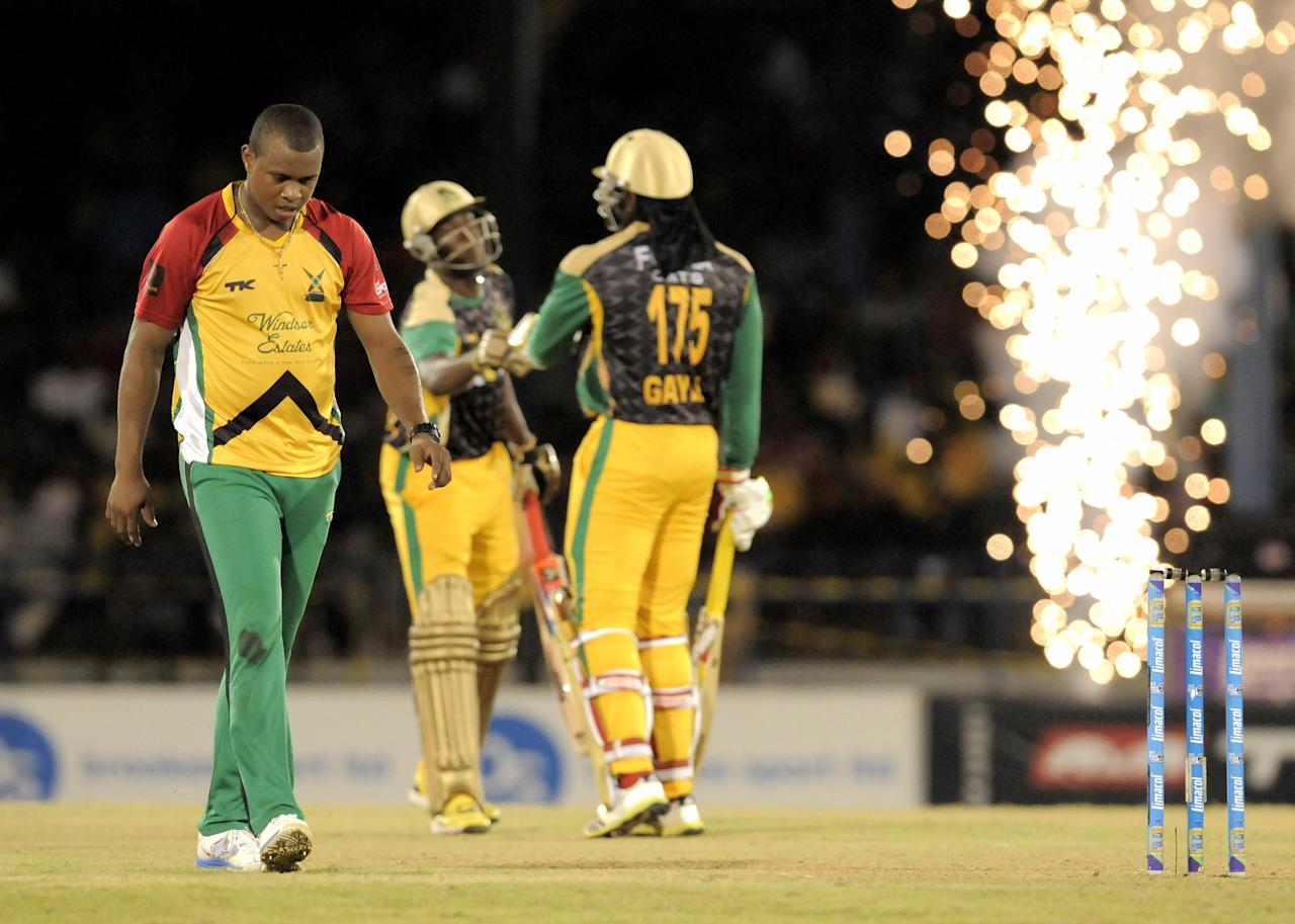 PORT OF SPAIN, TRINIDAD AND TOBAGO - AUGUST 24:  Christopher Barnwell (L) of Guyana Amazon Warriors goes for 4 off Jamaica Tallawahs Andre Russell (C) during the Final of the Caribbean Premier League between Guyana Amazon Warriors v Jamaica Tallawahs at Queens Park Oval on August 24, 2013 in Port of Spain, Trinidad and Tobago. (Photo by Randy Brooks/Getty Images Latin America for CPL)