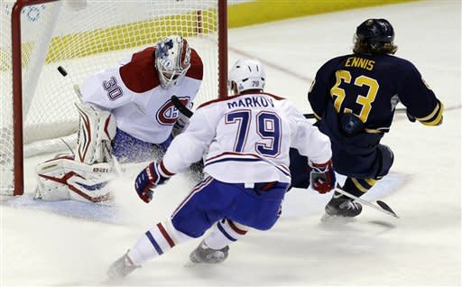 Buffalo Sabres' Tyler Ennis (63) scores on Montreal Canadiens goalie Peter Budaj, of Slovakia, as Canadiens' Andrei Markov (79), of Russia, defends during the second period of an NHL hockey game in Buffalo, N.Y., Thursday, Feb. 7, 2013. (AP Photo/David Duprey)