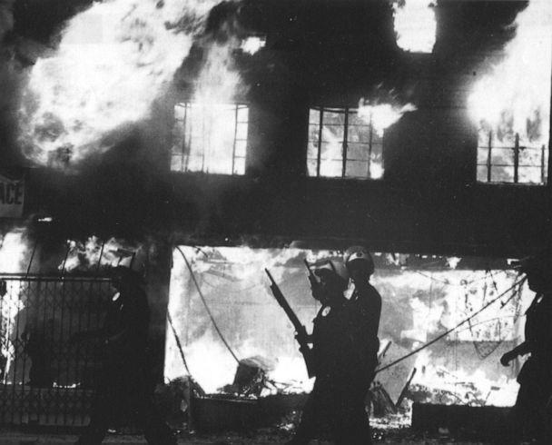 PHOTO: Police officers stand watch over burning building in West Los Angeles following looting and arson reaction to the acquittal of four LAPD officers in the Rodney King incident, April 30, 1992 in Los Angeles. (The Washington Post via Getty Images, FILE)